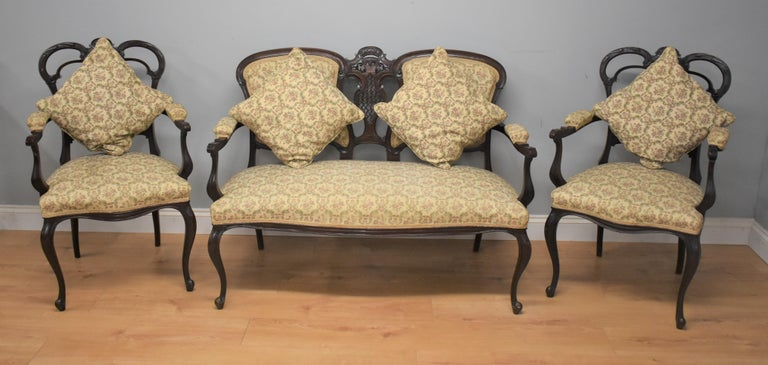 Edwardian mahogany three-piece salon suite comprising a two seat settee and two elbow chairs all with pierced back and standing on cabriol legs.
