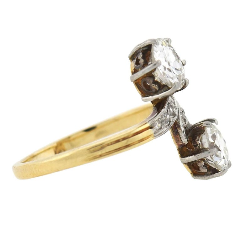 A unique and exquisite diamond bypass ring from the Edwardian (ca1910) era! Crafted in 18kt yellow gold topped with platinum, this piece features two old Mine Cut diamonds nestled together at the center, forming a stylish