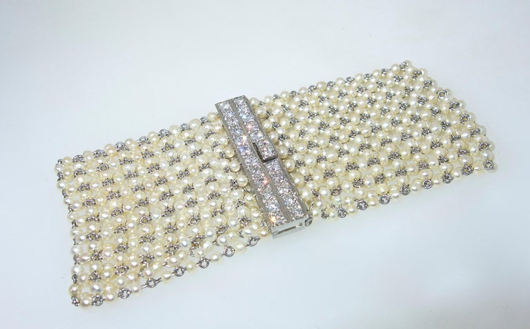 Natural pearls strung on platinum and accent with a fine diamond clasp.  This platinum bracelet made in the early 20th century is 7.25 inches long and 1.5 inches wide.  The natural oriental pearls are all well matched, circular and display a fine