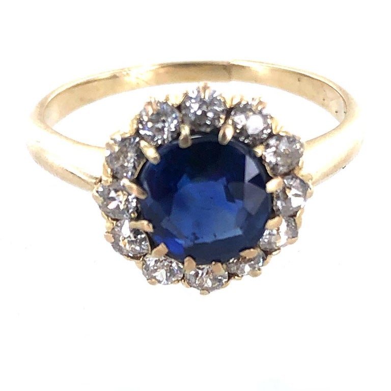 Exquisite Antique Blue Sapphire Diamond Ring. The center 1.56 carat blue sapphire has a certificate from the AGL stating no heat or treatment has been applied to the sapphire. Surrounding the bright blue sapphire are 12 Old Mine Cut Diamonds