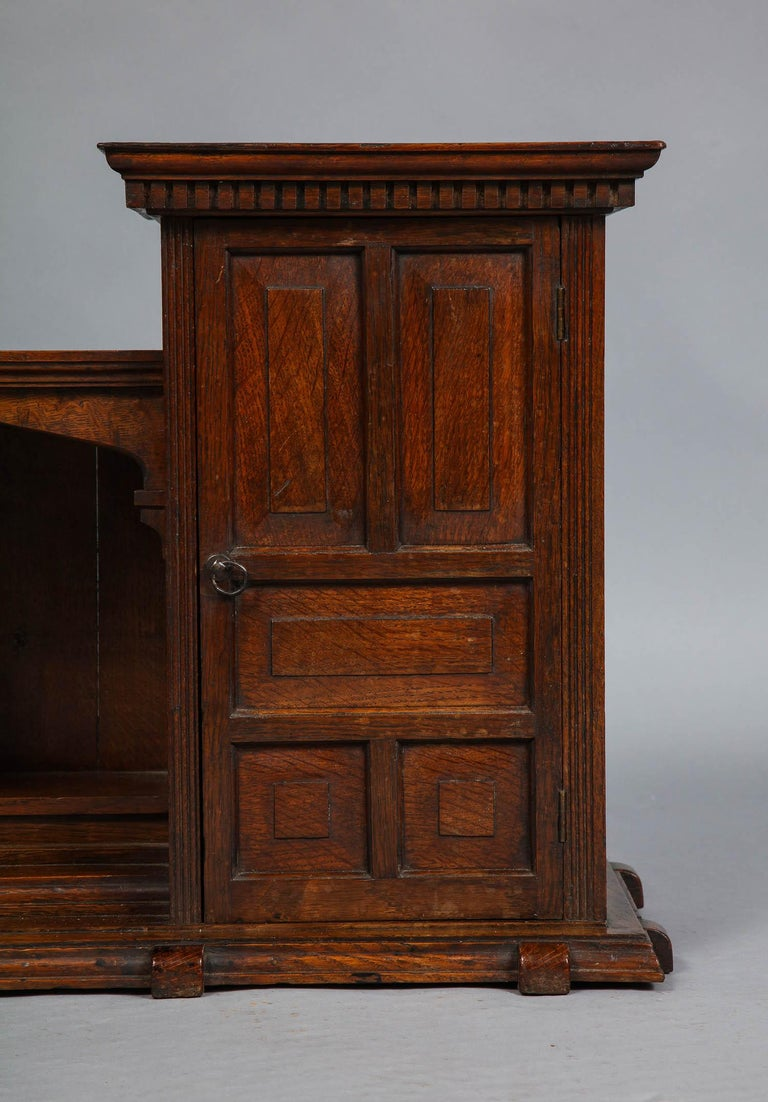 Fine late 19th century English oak hanging or desk cabinet, having two cupboards with paneled doors, dentil molding, and interior shelf flanking open niche with arched cubby, the whole of fine quality. This cabinet would function well either mounted