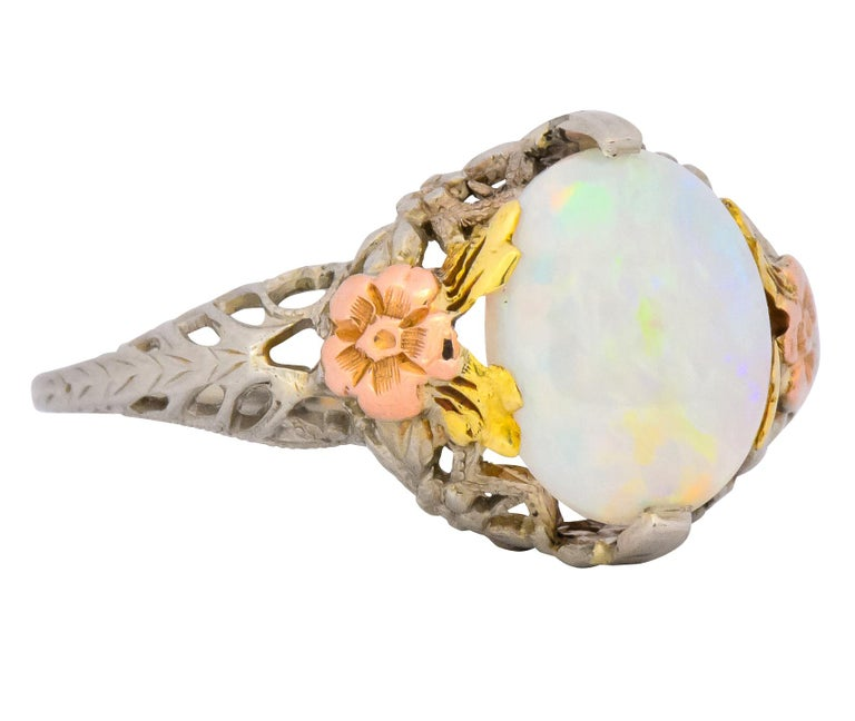 Centering a lovely cabochon cut white opal measuring approximately 10.0 x 9.0 mm  Excellent play-of-color, full spectrum in broad flashes, translucent with excellent polish and luster  Flanked by applied 14 karat rose gold flowers with yellow gold