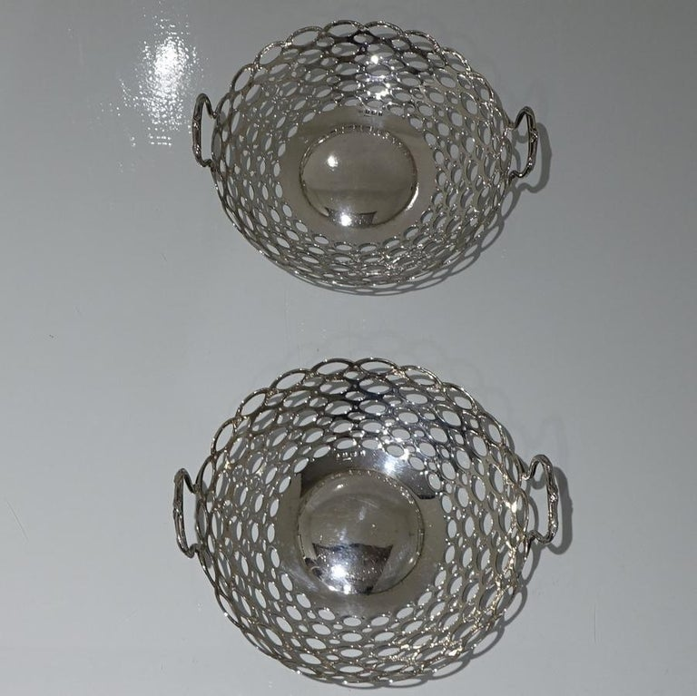 A beautiful pair of circular silver dishes decorated with elegant oval pierced walls and stylish incuse floating handles.     Weight 19.3 troy ounces/603 grams  Measures: Height 3 inches/7.5cm  Diameter 9 inches/23cm.  Condition: Excellent