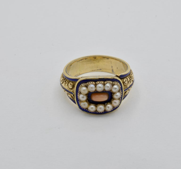 Six fresh water pearls border a pastel coral in the middle with intricate design and navy blue enamel. Engraved in the back this Edwardian ring dates 1824 and is from Mansfield Woodhouse, England. A piece of history, elegance, and charm, this ring