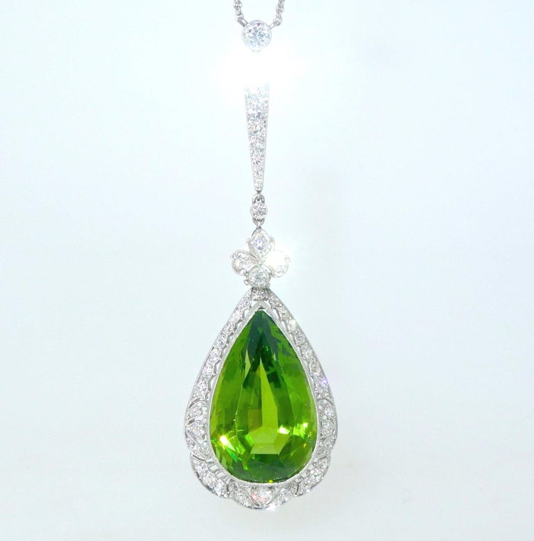 Edwardian pendant necklace centering a fine natural bright green peridot weighing approximately 19.5 cts.  Surrounding this pear cut stone are numerous European cut diamonds weighing approximately 1.6 cts.  This hand made platinum piece shows