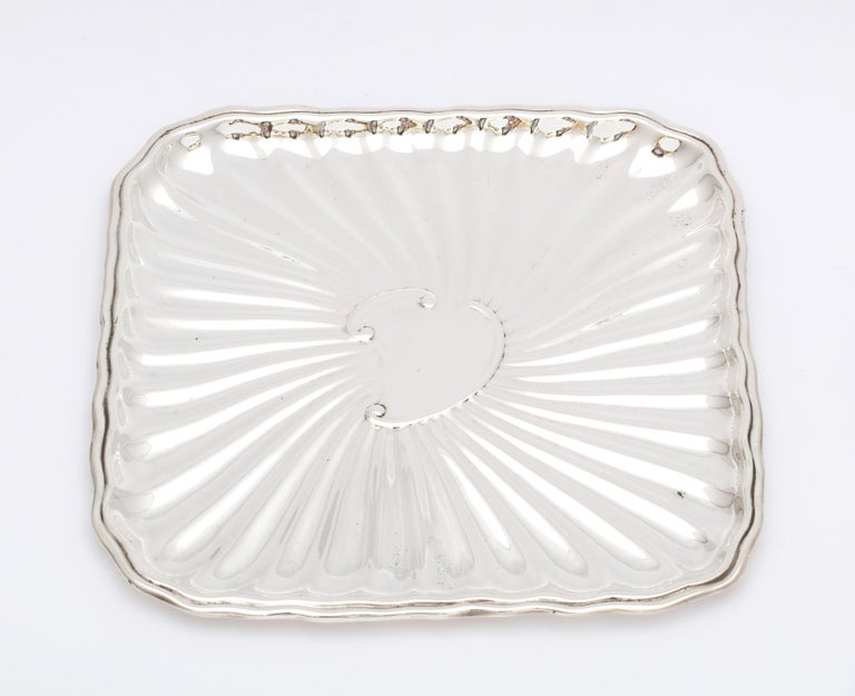Edwardian period, sterling silver card tray, J.E. Caldwell and Company, Philadelphia, circa 1915. Fluted design. Vacant cartouche. Measures 6 1/8 x 6 1/8 x 1/4 inch high when lying flat. Weighs 4.350 troy ounces. Dark spots in photos are