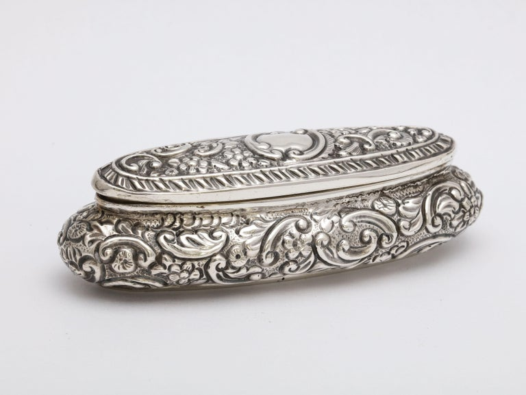 Edwardian period, sterling silver, oval trinkets box with hinged lid, London, 1913, Charles James Fox - maker. Measures 4 inches wide x 1 1/4 inches deep x 1 1/4 inches high. Weighs 1.185 troy ounces. Interior in gilded. vacant cartouche. Some very