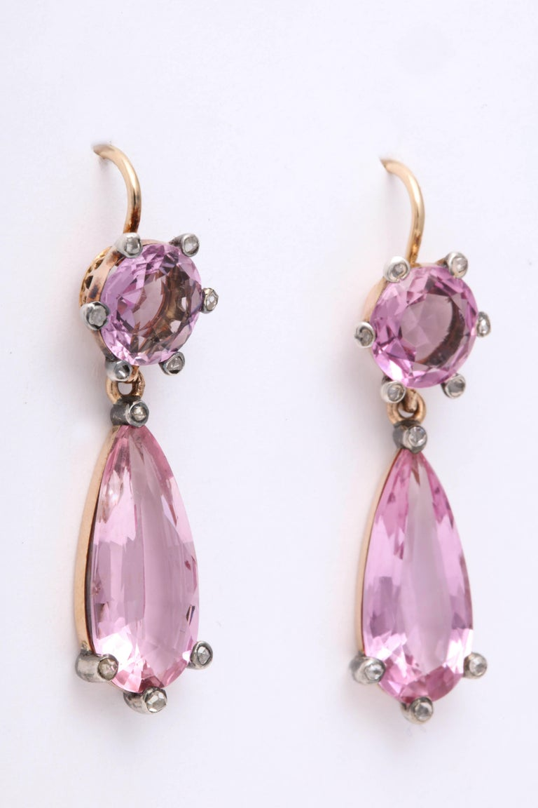 English dangle drop earrings with the most vibrant pink topaz in yellow gold. 10 small rose cut diamonds are set in silver on each earring.