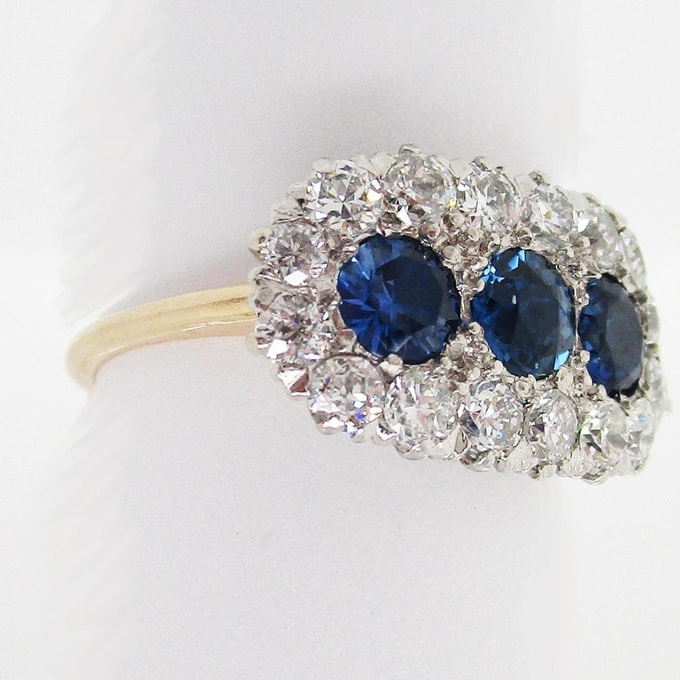 This is an absolutely breathtaking Edwardian ring in platinum and 14k yellow gold, featuring three stunning sapphires framed by a row of white old mine cut diamonds. This ring has a stunning unique layout and a gorgeous overall look! The ring has a