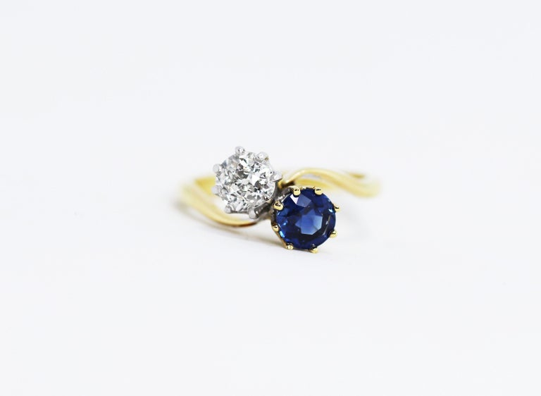 Beautiful Edwardian two-stone twist ring set with a natural blue sapphire weighing 0.87 carat and an old mine cut diamond weighing 0.75 carat. The diamond is set in a platinum 8 claw crown collet with the blue sapphire set in a 18 carat yellow gold