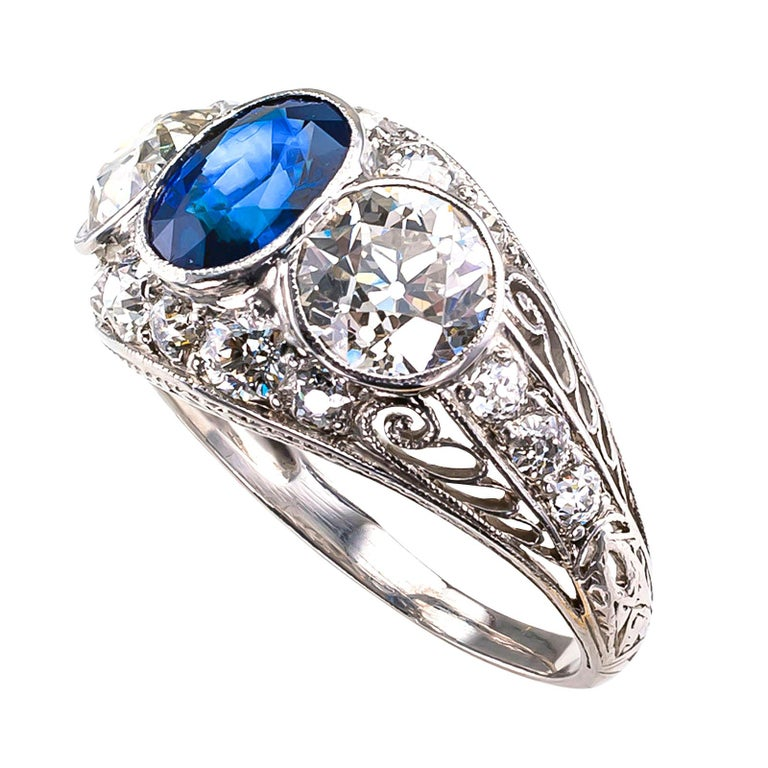 DETAILS:  Edwardian diamond and sapphire three-stone platinum ring circa 1910.  DIAMONDS: two old European-cut diamonds totaling 2.02 carats, accompanied by a reports from EGL-USA stating that the diamonds are I – J color and VS1 clarity.  SMALL