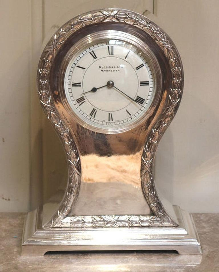 A heavy, well made silver plated balloon clock dating to the early 20th century. It has a waisted case with wheatsheaf edging and an ogee moulded base. The white enamel dial has a bevel edge convex glass and is signed by the original retailers