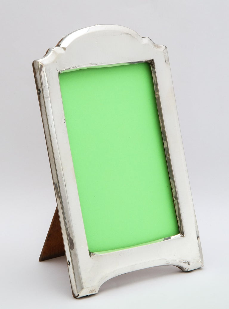 Edwardian, sterling silver, hump-top picture frame with wood back, Birmingham, England, year-hallmarked for 1915, James and John Deakin (James Deakin and Sons) - makers. Measures 8 1/4 inches high at highest point x 5 inches wide x 6 inches deep
