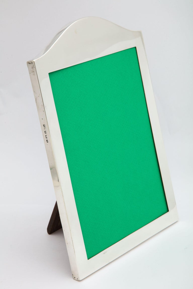 Large, Edwardian, sterling silver, hump-topped picture frame with wood back, Birmingham, England, 1915, Mappin and Webb - makers. Measures 10 inches high (at highest point) x 7 1/4 inches wide x 4 1/2 inches deep when easel is in open position. Will