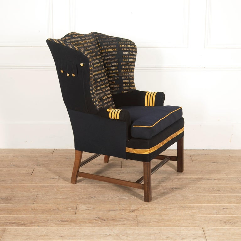 Stunning Edwardian wingback armchair.   This chair has great scale and proportions, with enclosing wings and a deep seat supported on square legs.  It is covered in hundreds of Royal Navy tally ribbons and an officer's uniform. The ribbons