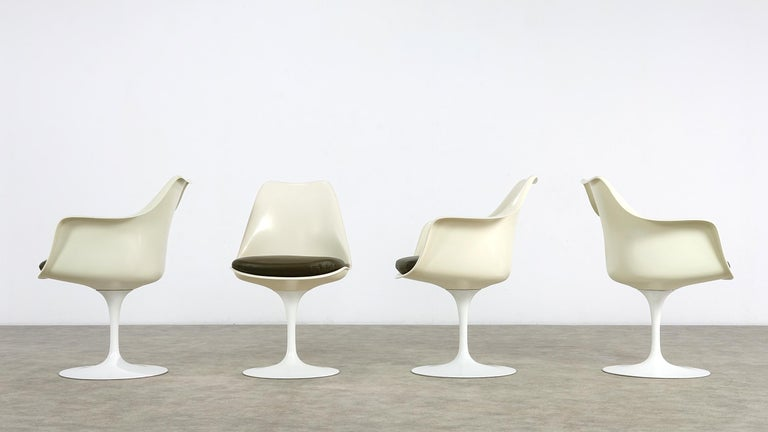 The design classic of the modern age in a very early version. The leather cushions were newly made. The three armchairs can be turned the sidechair is fixed.  Frame: cast light metal with plastic coated seat shell: moulded polyester shell.