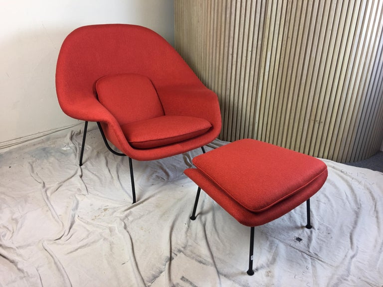 Nice early example from 1950s, cap style feet model. Newly upholstered in a red nubby weave fabric. Fiberglass body with metal frame work and legs. Said to comfort comparable to a Mother's Womb. In all honesty I think it is the most comfortable
