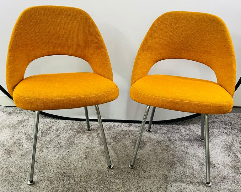 A pair of Mid-Century Modern side chairs designed by Eero Sarrinen (Finnish/American, 1910-1961) for Knoll Associates, USA. The chairs are finely upholstered in a stylish turmeric orange tone. The chairs are marked with the manufacturer label