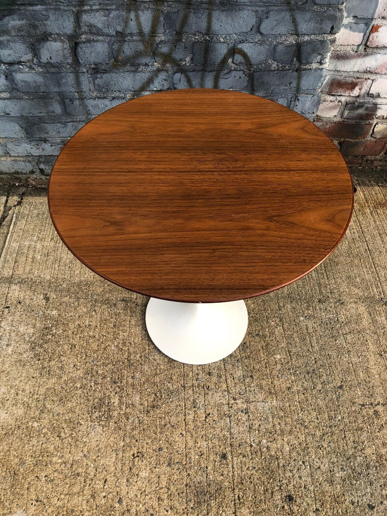 Stunning walnut side table. 20 in diameter circular wood top finished in walnut. Like new original surface. Retains original early Knoll bow tie label on underside. Cast iron base is very heavy and sturdy. Base has been repainted. Table is extremely