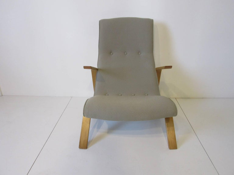 An upholstered grasshopper lounge chair in a seafoam green fabric with birch wood sculptural arms and legs, a early vintage version of this icon chair. Manufactured by Knoll.