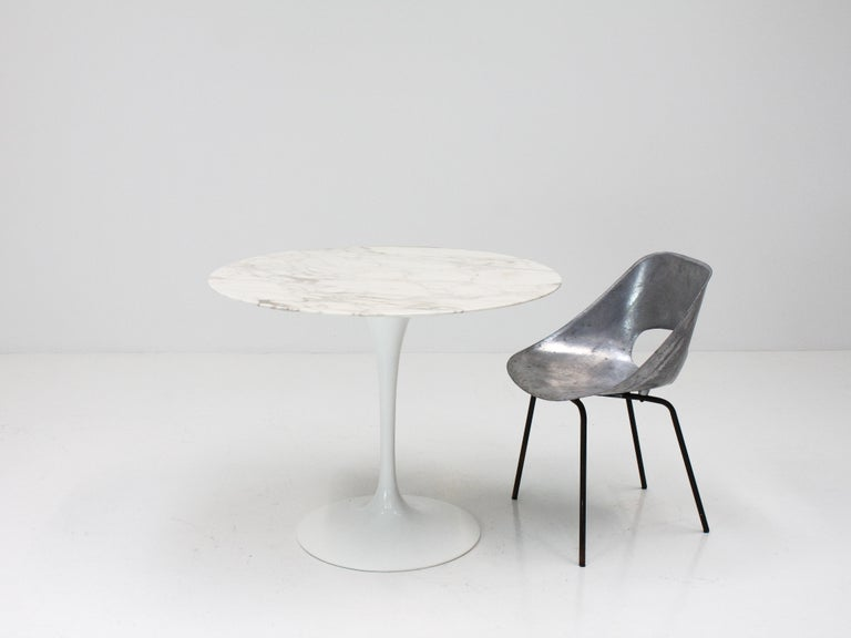 A hugely iconic and famous Eero Saarinen design, the Tulip dining table with its characteristic sculptural single stem with this piece featuring a beautiful veined Italian Calacatta marble tabletop.