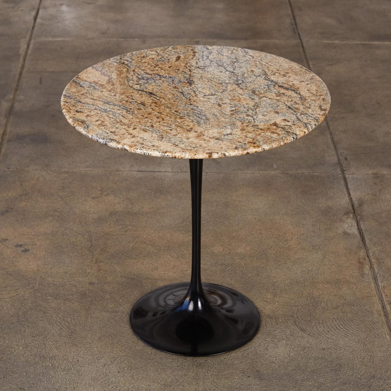 One of Saarinen's most enduring designs, part of the Pedestal Collection and designed in 1957, this side table features a black heavy molded cast aluminum base with a round light brown and black veined granite top.