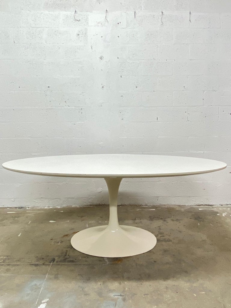 Rare, early edition 1960s Eero Saarinen white oval laminate top with lacquered cast iron base dining table produced by Knoll. Maintains original Knoll Associates label on underside.