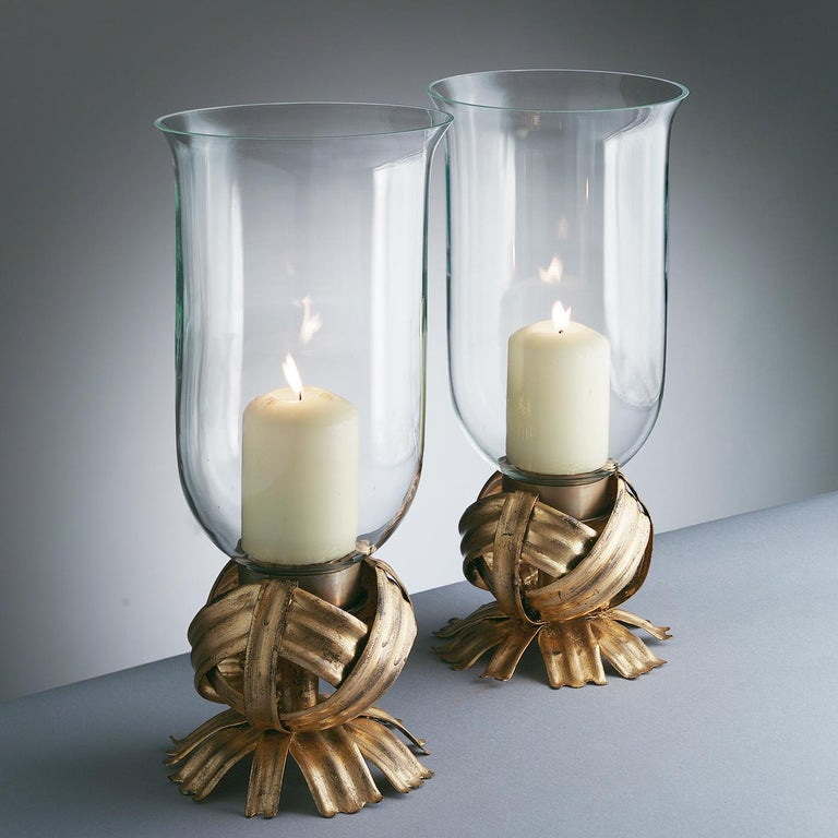 This splendid hurricane candleholder is a superb accent for a special outdoor dinner. The delicate glass bowl with curved edges rests on a striking forged iron base shaped by skillful craftsmen to evoke the silhouette and texture of a ball of yarn,