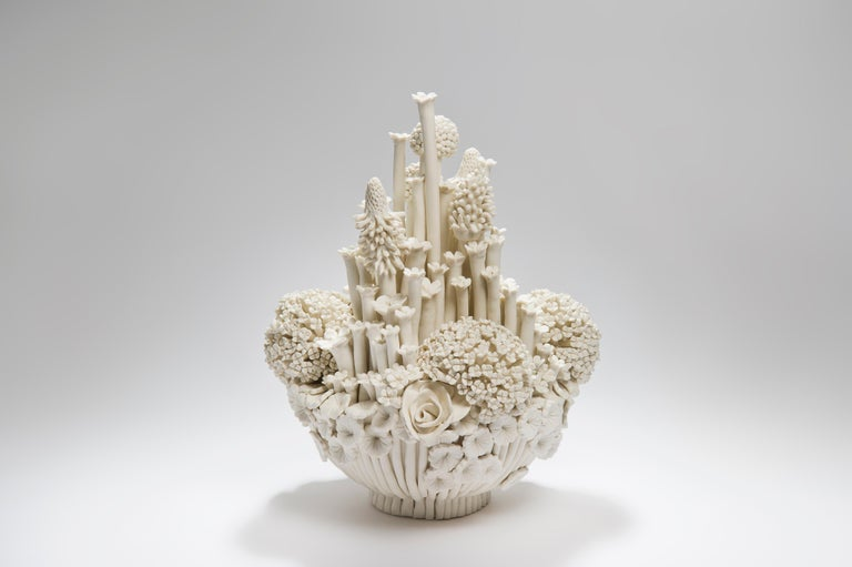 Efflorescence I, is a unique handcrafted porcelain sculpture completely covered in a multitude of individually made porcelain flowers of all different shapes and forms by the British artist Vanessa Hogge.  Vanessa Hogge breathes life into her clay