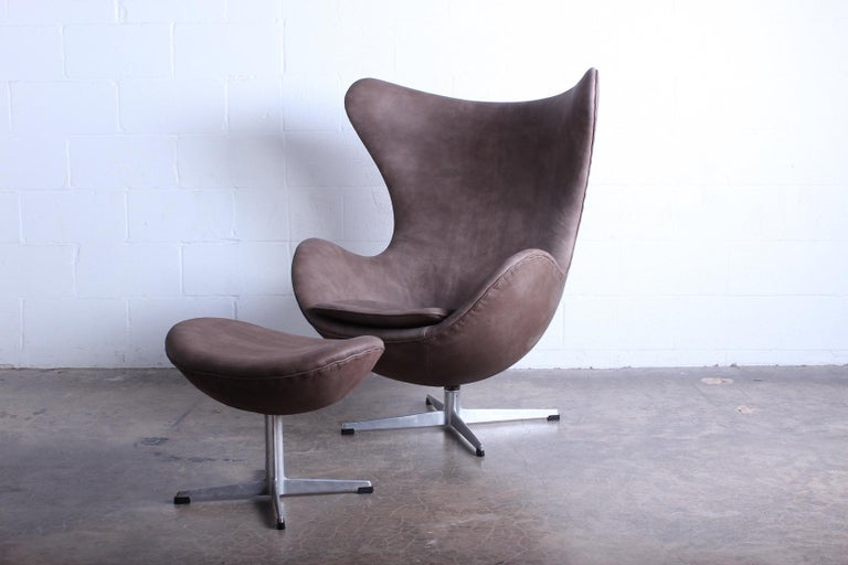 A leather egg chair and ottoman designed by Arne Jacobsen for Fritz Hansen.