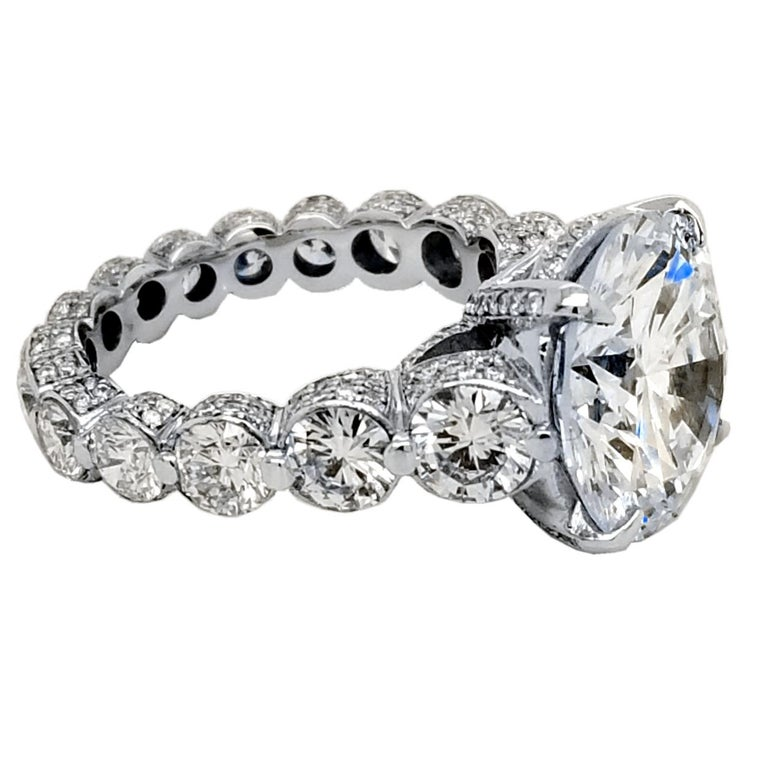 A Beautiful shiny Round Brilliant H/SI1 EGL certified center Diamond set in a fine 18k gold Eternity style Engagement Ring with Pave set diamonds all over and Shared Prong set Rounds on the shank. Total diamond weight of 4.16 Ct.  on the side. Total