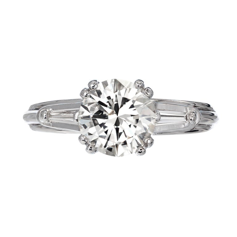 Three-stone round and baguette diamond engagement ring. This diamond faces up white and very bright. Ideal European modern cutting style. 1.51ct,  . Handmade wire setting. This diamond is certified and graded by the EGL. Handmade raised double prong