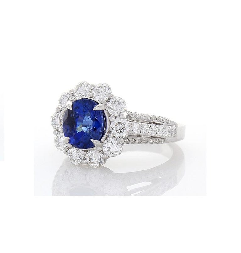 This cocktail ring features a 3.08 carat, oval cut, blue sapphire in the center with measurements of 8.30x7.5mm. The gem source is Sri Lanka; its color is a perfect royal blue; its luster and transparency is excellent. A stunning halo cluster of