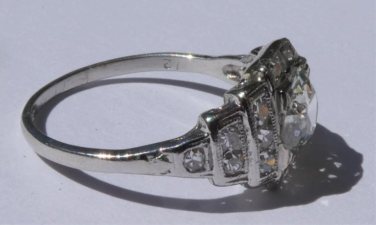 The lovely Art Deco engagement ring was crafted circa 1920 in platinum in a geometric design. It is hallmarked platinum and comes with an EGL USA diamond certificate stating: Center diamond 1.04 carat Shape and cut Old European Colour Grade