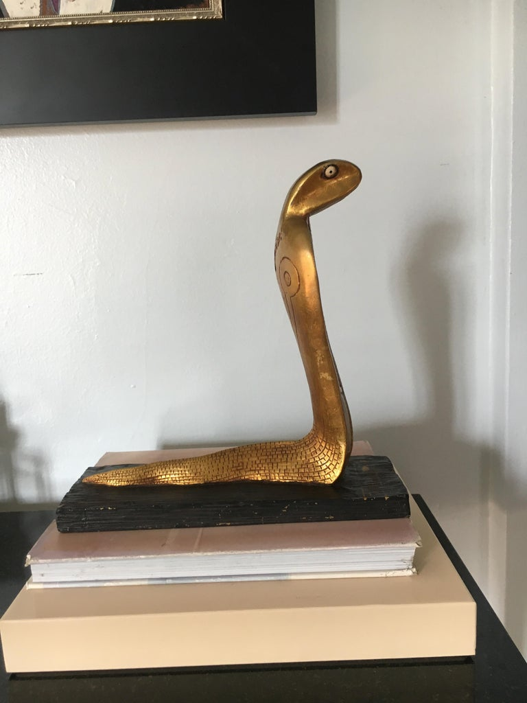 Gilt cobra sculpture bookend, a handsome decorate piece, the snake portion is likely plaster, or perhaps carved wood, with a striated wooden painted base, the piece has Egyptian hieroglyphics on the serpent and base.