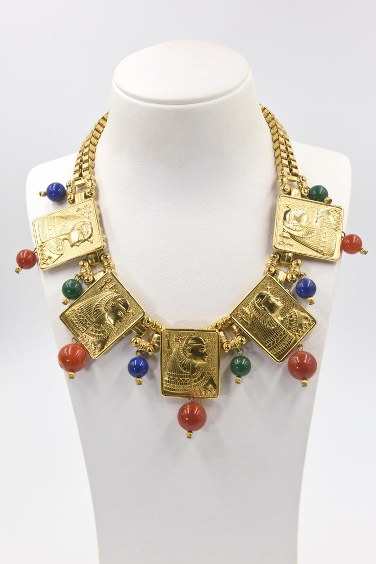 Stunning Egyptian Revival necklace featuring high relief plaques of Cleopatra accented with blue, orange and green beads.  The necklace has 5 plaques with dangling orange sunstone beads.  Between the plaques are double bridges to a rectangular link