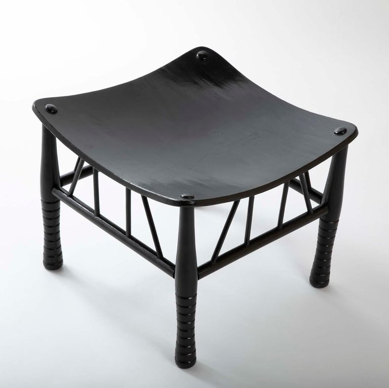 19th century English Thebes stool with ebonized lacquer finish, the solid seat supported by four turned legs united by stretchers. A fine example of the form, unusual in it's rich black surface. The original Egyptian Thebes stool dates back to the
