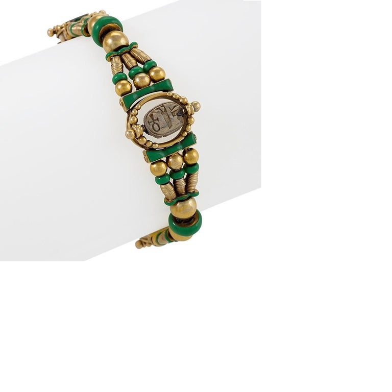 An Egyptian Revival bracelet, circa 1860, in 18 karat gold with green enamel framing and beads. The bracelet features three faience scarabs; two smaller, flanking insects in teal, and one large scarab in earthen tones at the center of the piece.