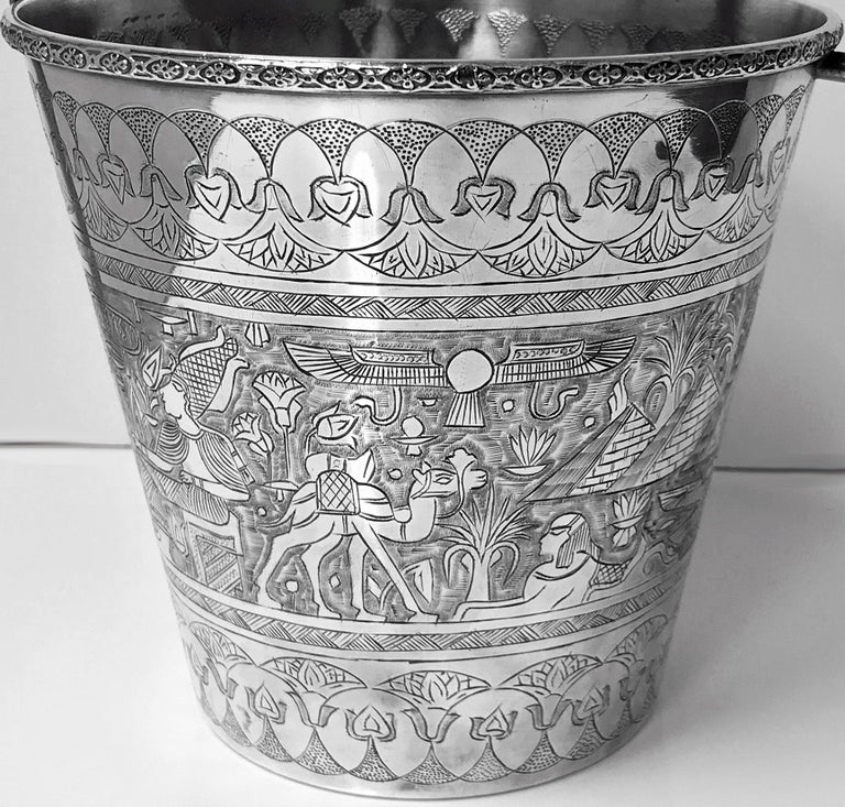 Egyptian silver wine bucket, circa 1920. The bucket of tapered form, richly engraved with multiple hieroglyphic depictions and pyramids, figures, horse's chariots, snakes, serpents, camels, wing handle. Marks for Cairo under base. Measures: Height: