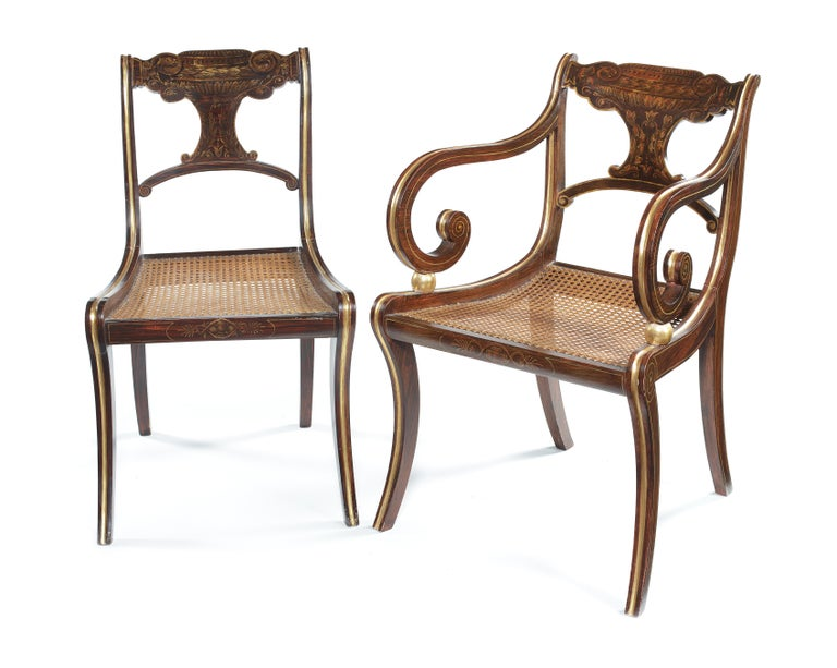 A set of six Regency faux rosewood, parcel-gilt decorated dining chairs with a matching pair of later open armchairs The pierced backs with moulded top rails and shaped splats and cross-rails above caned seats with squab cushions, on inswept legs,