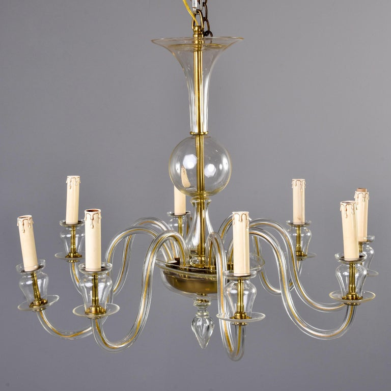 Murano chandelier in pale amber glass with eight arms and candle style lights with candelabrum sized sockets, circa 1960s. New wiring for US electrical standards. No flaws found. Unknown Murano maker.