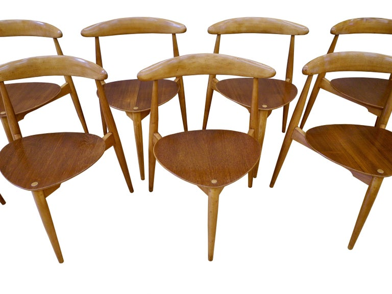 This set of eight Danish modern stacking dining chairs are made of teak and beech. The