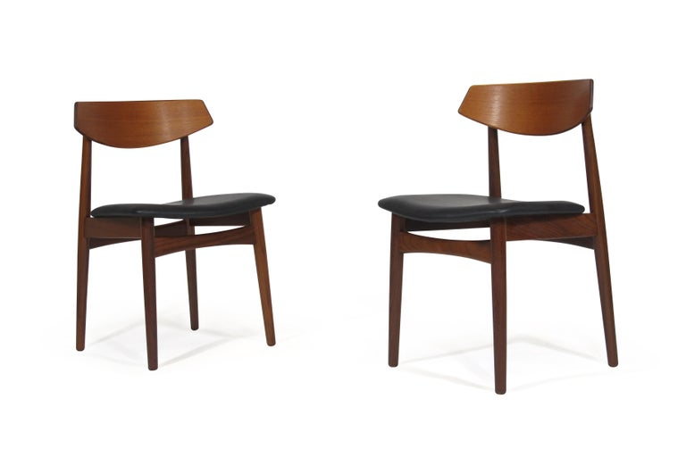 Eight midcentury teak dining crafted of solid old-growth teak frames, sculpted back rest with newly upholstered seats in black leather. Manufactured in Denmark during the early 1960s. The wood has been professionally restored in a hand-rubbed