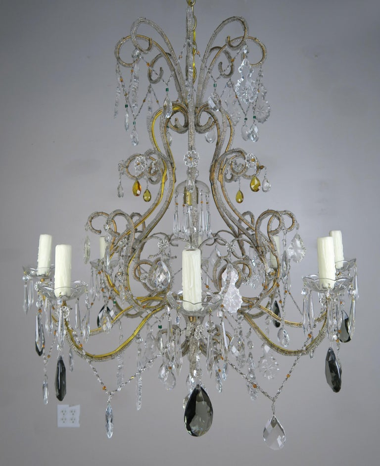 Eight light Italian crystal beaded arm chandelier with scrolled arms ending in drip wax candles. A large smokey crystal hangs from each arm and are combined with clear crystals throughout. The chandelier is newly rewired and includes chain and