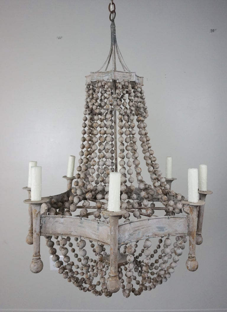 Eight light soft gray painted wood beaded and metal chandelier. The fixture is newly rewired with drip wax cream colored candle covers. Garlands of wooden beads drop down to create a beautiful basket shape. Chandelier includes chain and canopy and