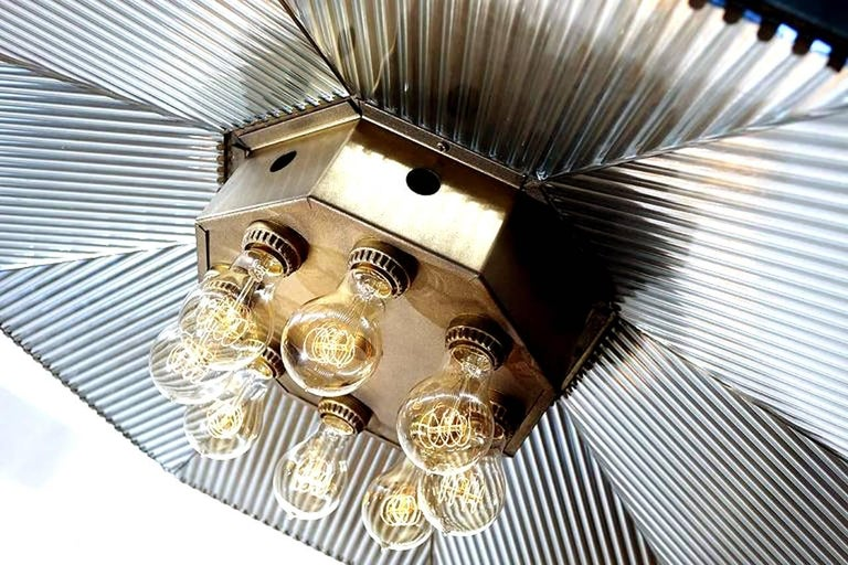 This is a large handmade mirrored reflector in the Frink style. The diameter of this octagon is over three foot with a central eight bulb cluster. They don't get showier than this. We have added the brass rods so it can hang to a drop length you