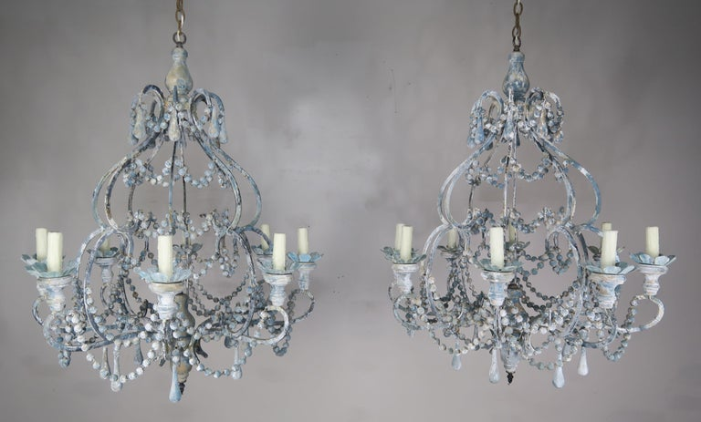 Pair of eight-light wood beaded and metal chandeliers with garlands of painted balls, blue tear drops and wooden bobeches throughout. The fixtures are newly wired with cream colored drip wax candle covers and include chain and canopy. We are now