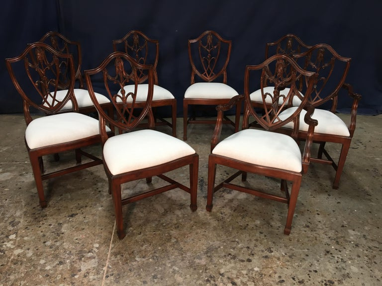 This is a set of eight (two arms and eight sides) mahogany Shieldback dining chairs by Leighton Hall. They feature the classic shieldback design with square tapered legs. They feature our standard medium brown mahogany color. The chairs come with a