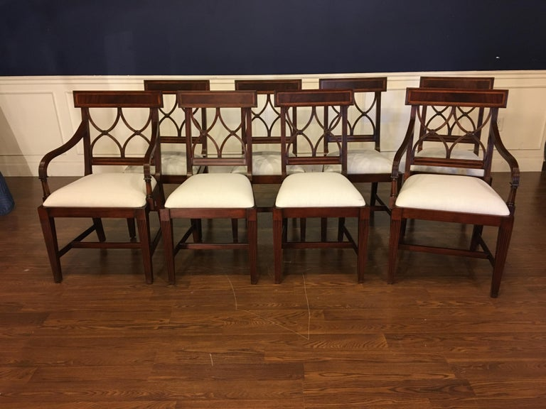 These are new traditional mahogany dining chairs. Their design was inspired by dining chairs from the Regency period. They feature classic Adams styling. They have an understated elegance with square tapered and fluted legs and delicate inlays in