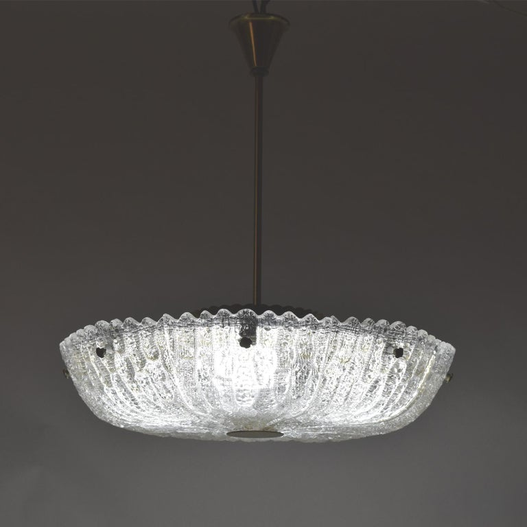 Mold-blown glass Orrefors ceiling lamp, with brass diffuser, rod and decorative screws. Designed by Carl Fagerlund.